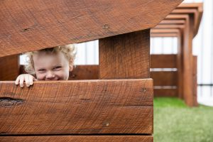 a cute kid in the wooden house of nido child care centre in seven hills